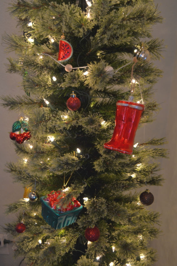A pencil tree lit up with garden themed vegetable and fruits and red garden boots