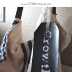 A Pinterest image of with an image of a linen bag with a faux leather bag tag with floral letters spelling growth