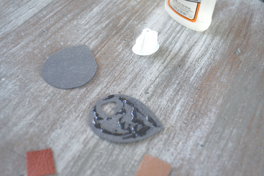 A tear drop faux leather earring turned over with gorilla glue drizzled on top ready to be bound with the backer