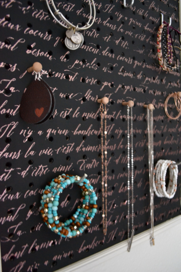 A black chalk painted pegboard close up with copper French scripting with bracelets, earrings and necklaces hanging from the pegs