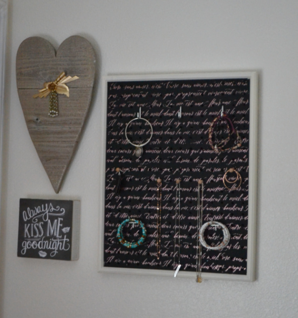 "A gallery wall with a wooden heart, a sign that says ""always kiss me goodnight"" and a rectangular jewelry wall organizer with jewelry hanging from the pegs"