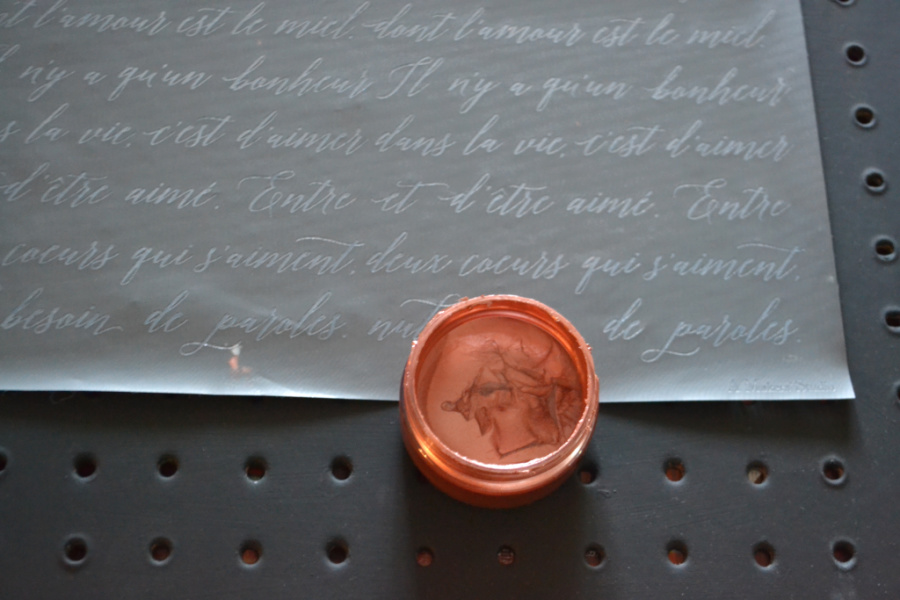 A copper ChalkArt tub sitting on a black painted pegboard with a french script mesh stencil on top