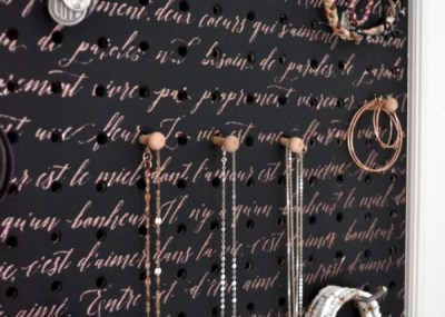 A close up of a black painted pegboard with copper scripting with necklaces, bracelets and earrings hung from the hooks