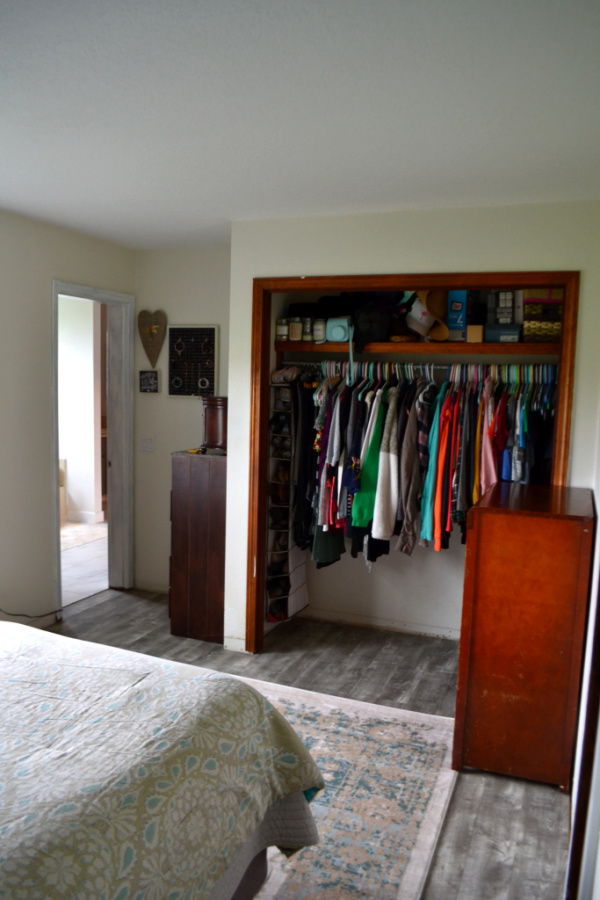 An open closet with a dresser on the right, with a view of the end of a bed on the lower left and a view into a bathroom on the upper left