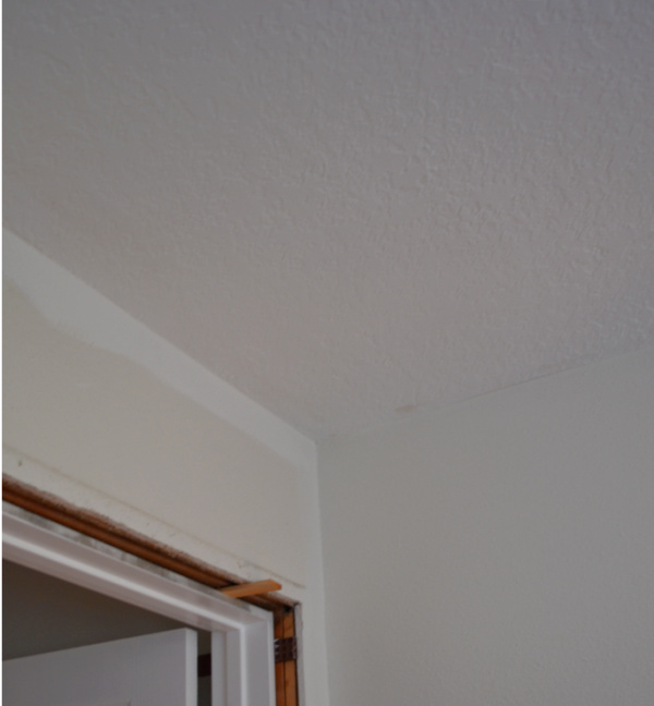 "The corner of a bedroom with a white painted ""cut-in"" against a dingy white wall"