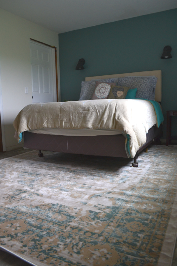 View of a queen size bed from near the floor with a blue, white, gold flecked rug on the lower half of the picture