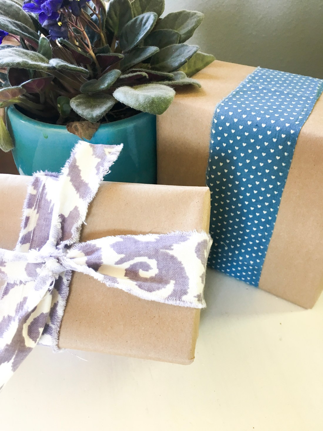 Two presents wrapped in brown kraft paper and tied with fabric ribbon, one with a bow and the other not