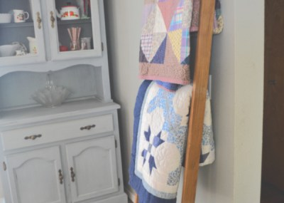 A finished blanket ladder leaning against a wall with three different quilts hanging from the rungs with a blue hutch in the background