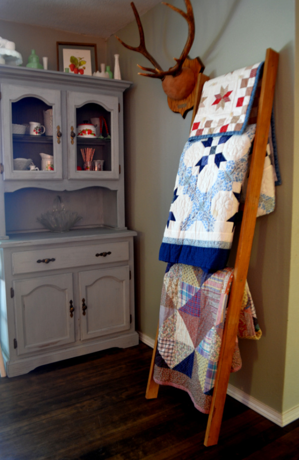 A finished blanket ladder leaning against a wall with three different quilts hanging from the rungs with a blue hutfch in the background