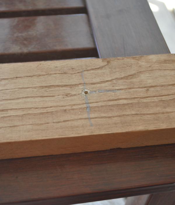 A close up view of a piece of wood with pencil marks and a hole drilled into the center of the pencil marks