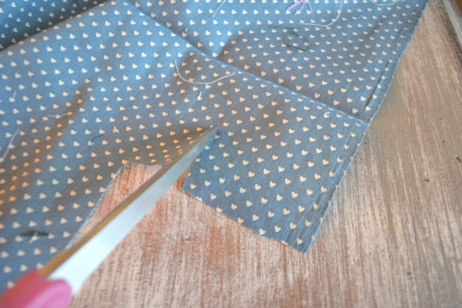 Blue fabric with small hearts spread out and a close up shot of a tip of scissors cutting into the fabric about 2 inches in from the edge