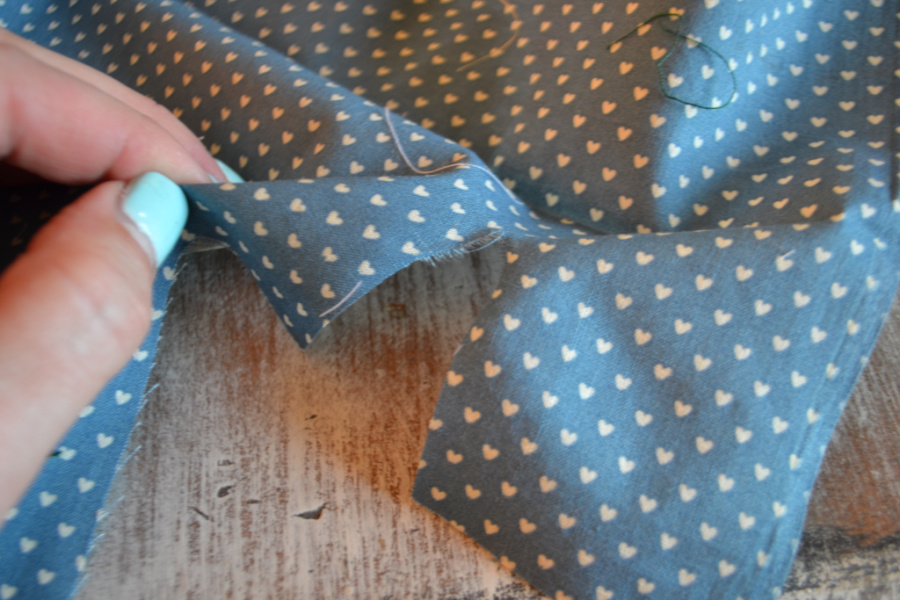 Blue fabric with small white hearts being torn