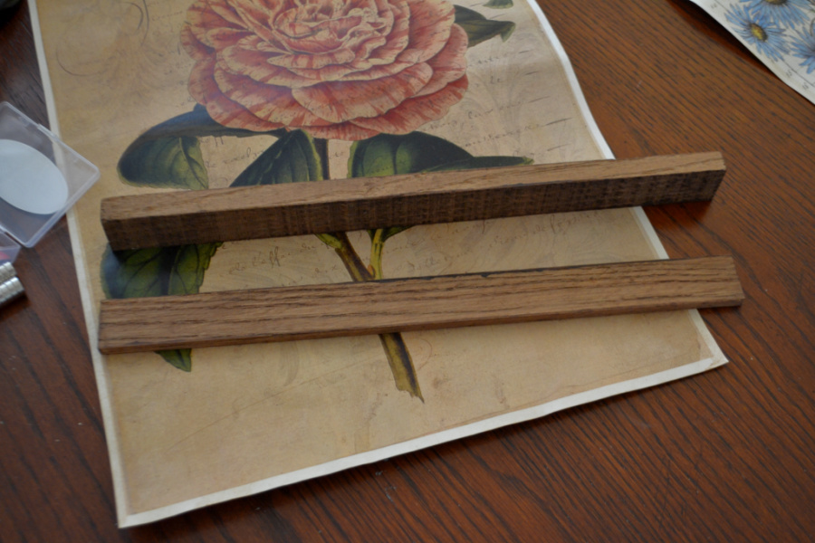A vintage rose paper print laying on a dark stained wood table with two pieces of stained trim laying toward the bottom on top of the print itself