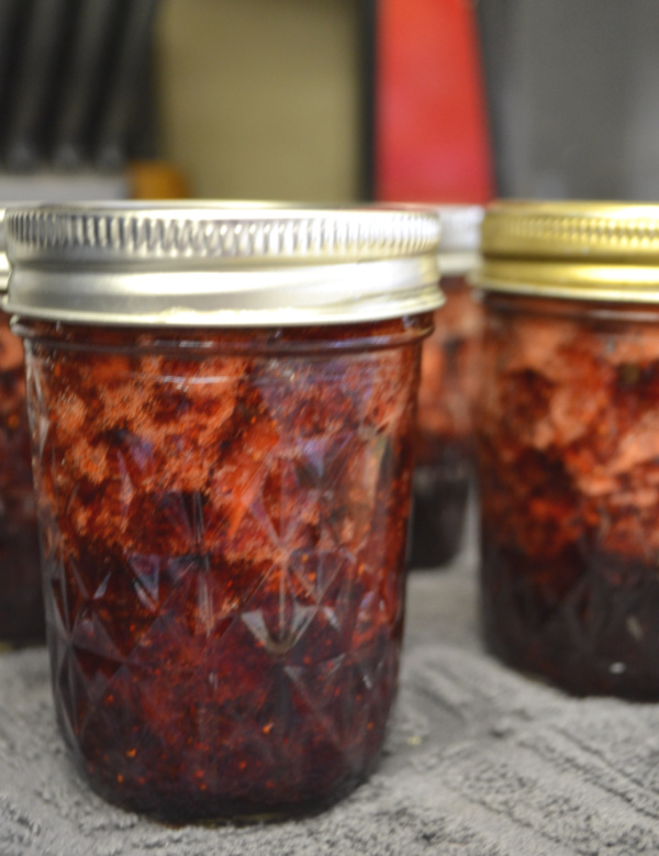 A close up of a strawberry jam jar sitting on a blue towel