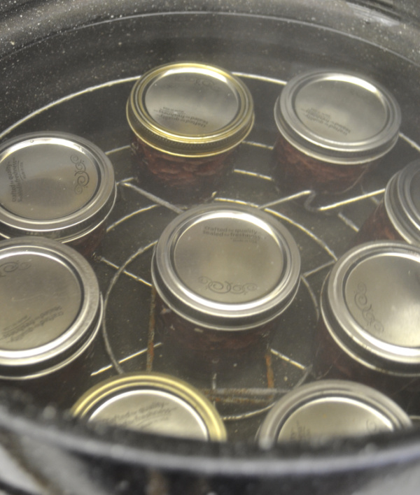 An above view of a water canner filled with jam jars ready to be preserved