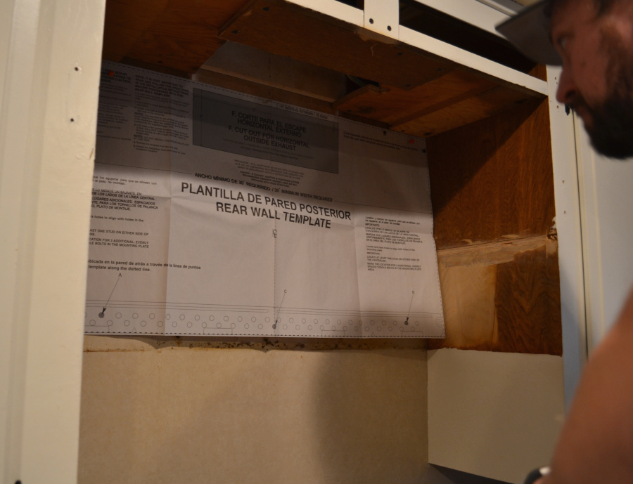 Looking into a space above a stove with a paper template taped to the wall