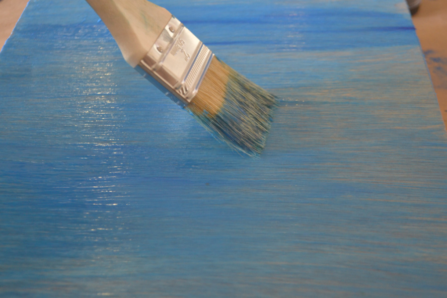 A piece of wood covered in blue wax with a paint brush in action swiping across the surface