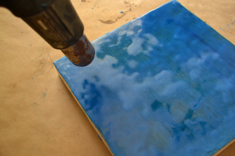 A heat gun is being used to melt the wax on the surface of wood