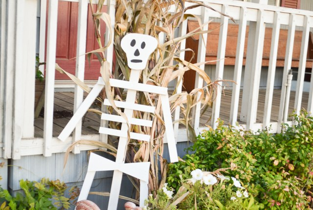 A white wood skeleton leaning against an outdoor wood staircase with a black painted face