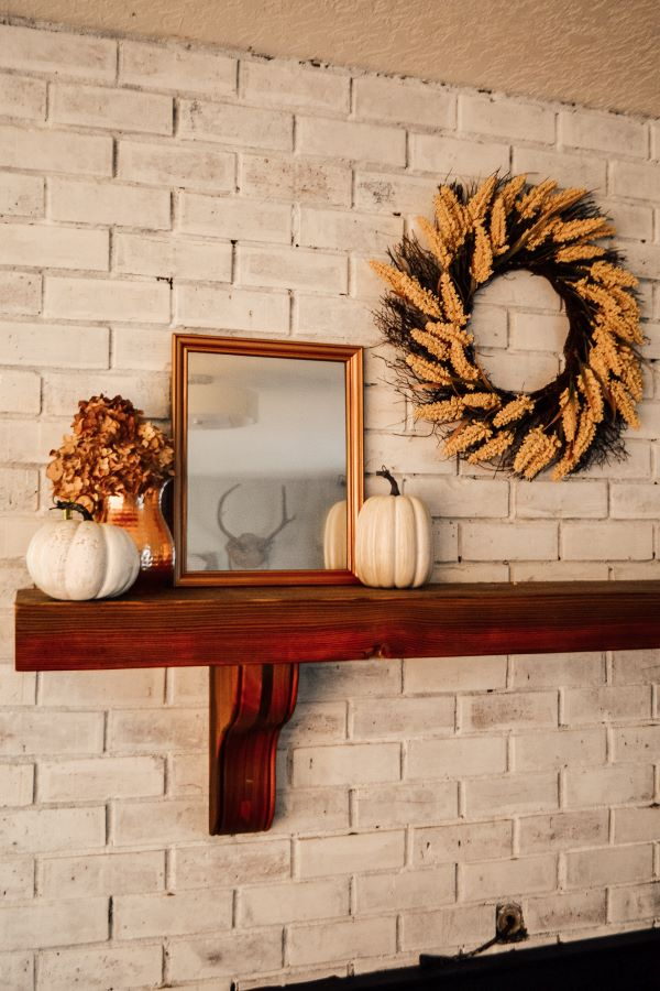 A white brick fireplace with a dark wood mantle with Fall decor of pumpkins, copper pitcher, and a DIY antique mirror
