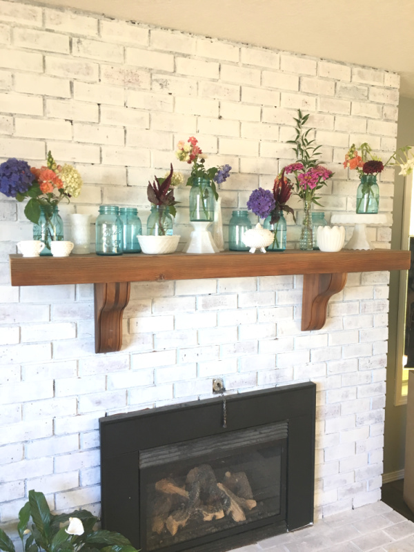 A straight look at a fireplace mantel on a brick fireplace with a green wreath hanging on the fireplace