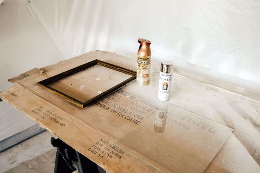 A piece of cardboard on sawhorses with a wood frame and piece of glass on top sitting next to copper and mirror effect spray paint bottles