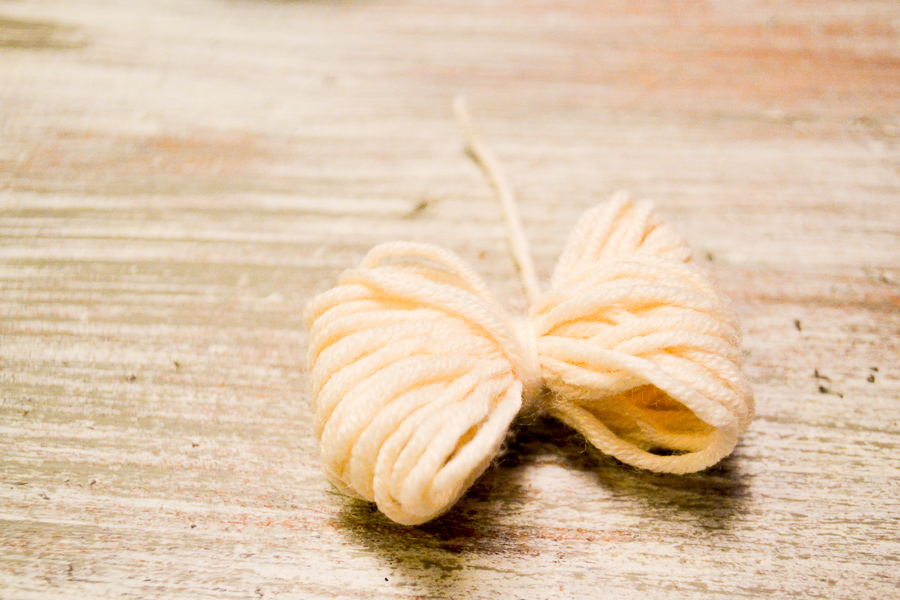 A tied yarn bow sitting on a white washed table