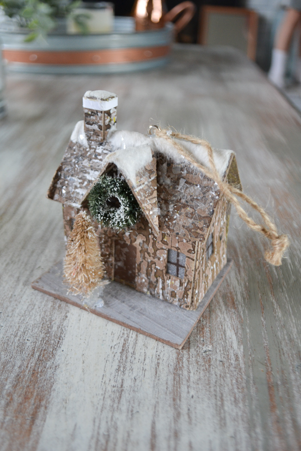 A small brown cabin ornament with a tree and a wreath on the front with a hanger out the top