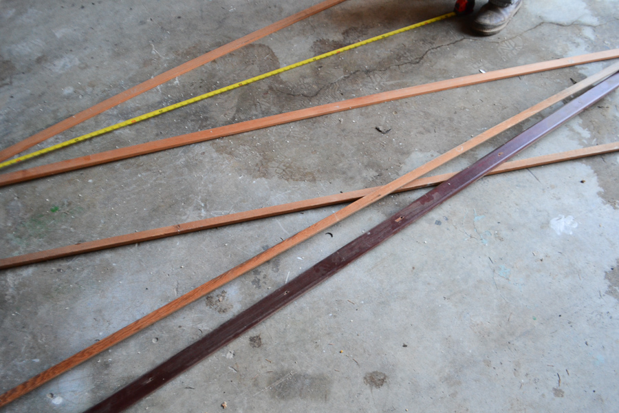 A picture of a concrete shop floor with scrap wood trim laying out with a tape measure