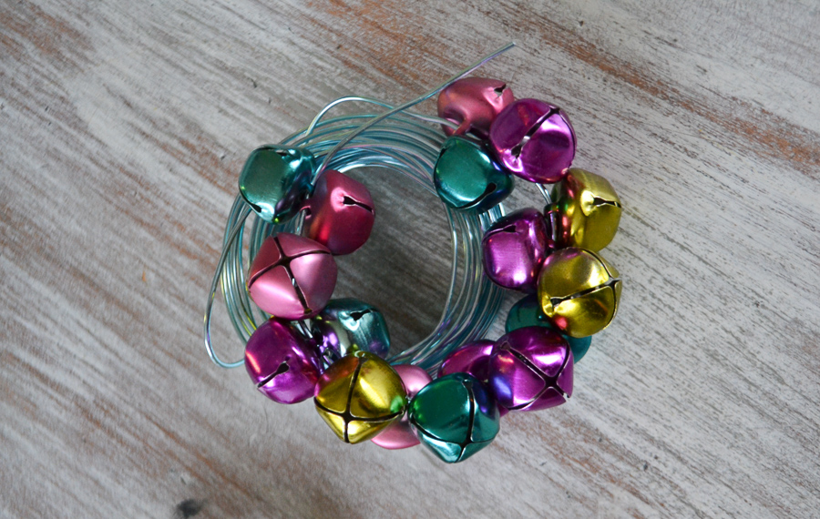 Wrapped blue wire with pastel colored jingle bells on the wire sitting on a whitewashed tabletop