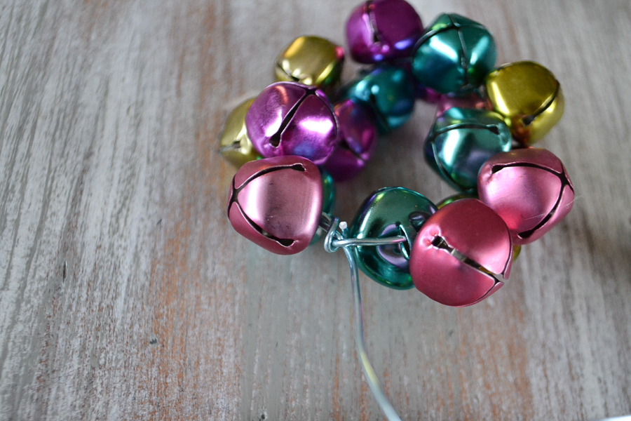 Large pastel jingle bells on a light blue wire in the shape of a circle