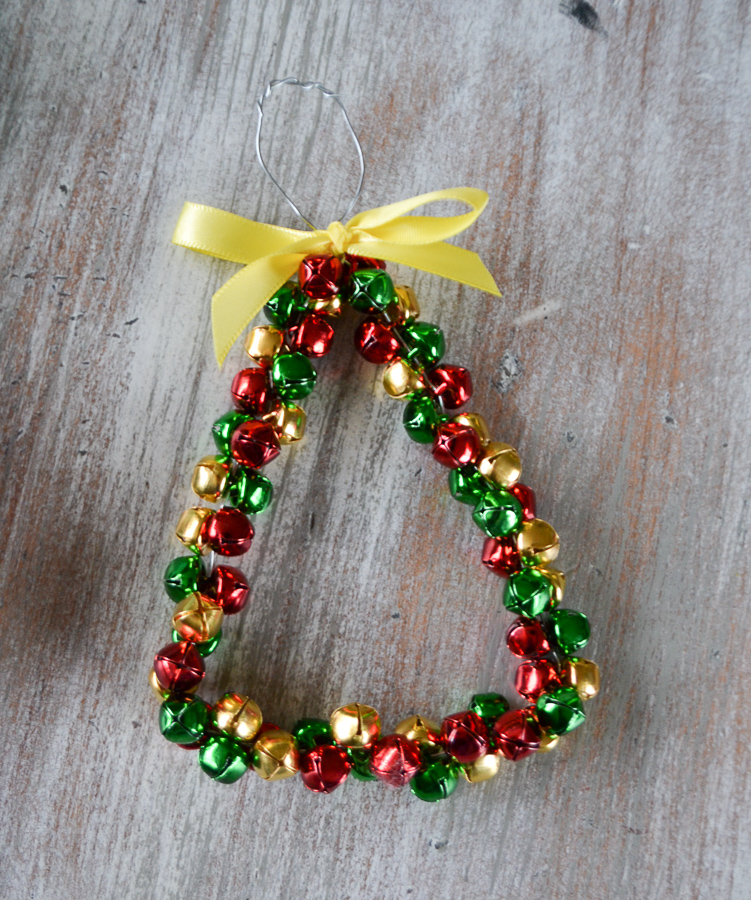 A triangle jingle bell ornament with a yellow bow on top