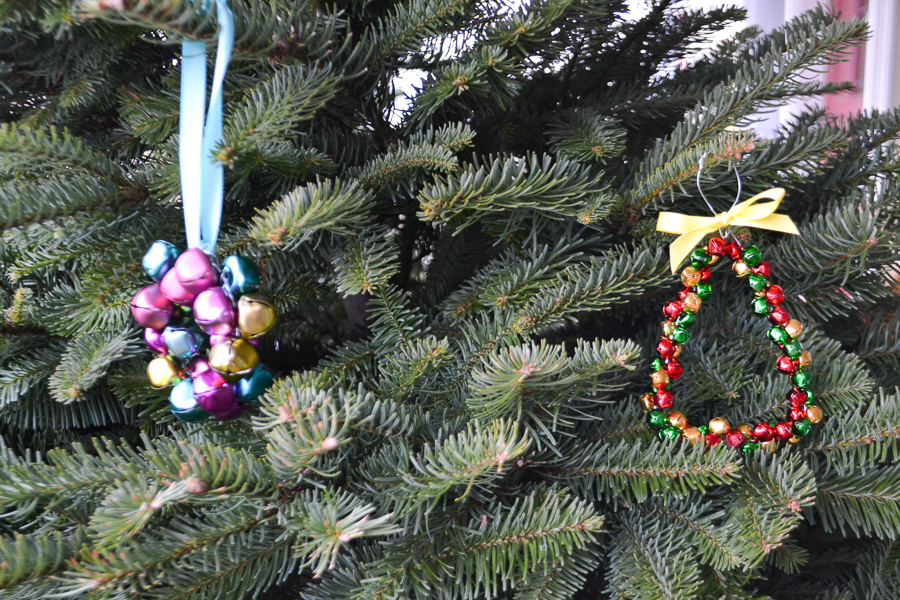 Two jingle bell ornaments hanging on a Christmas tree