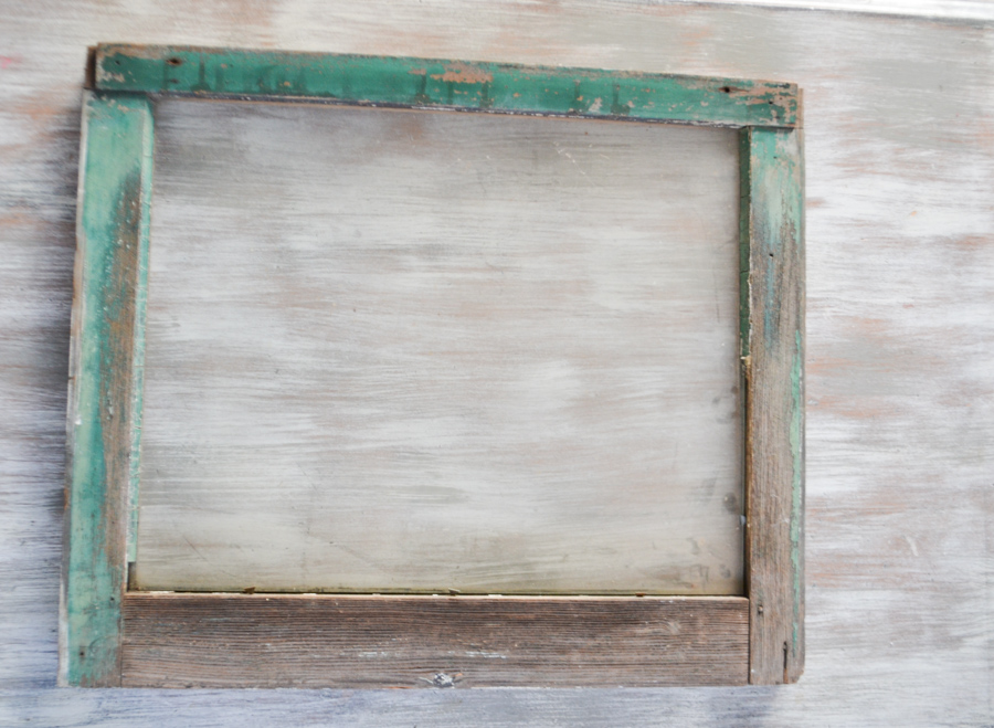 A green chippy painted window frame laying on a dry brushed tabletop