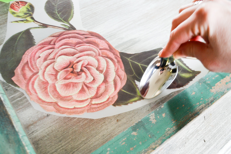 A close up of a flower ink transfer being rubbed with the back of a household spoon