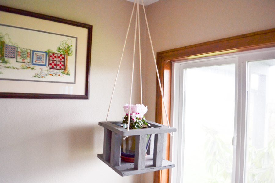 A wooden square plant stand hanging from a ceiling in the corner of a room with a window the right and wall behind it