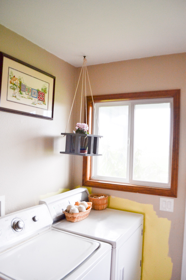 A wooden plant stand hanging above a washer and dryer in the corner of a room with a window in the background
