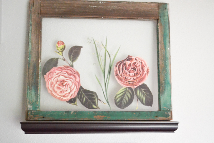 A close up of an old window pane with chippy green paint and pink flowers that are rub on ink transfers applied to the glass