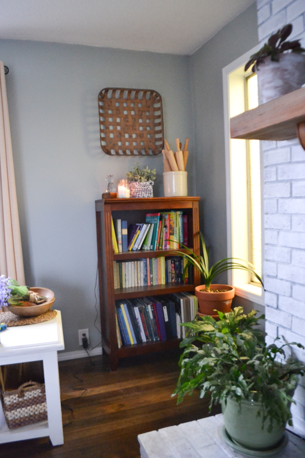 A dark wood bookcase against a gray wall with a white brick fireplace in the foreground