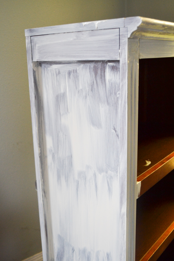 A streaky painted side of a bookcase with white paint