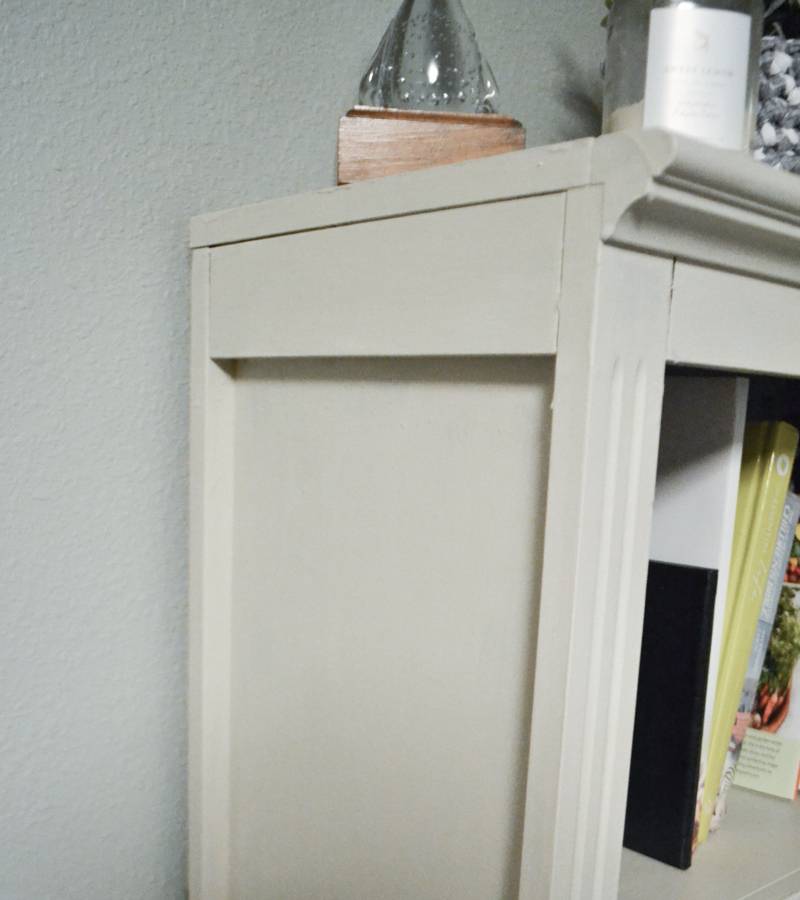 A close up picture of the side of a bookcase that has been painted with white chalk paint