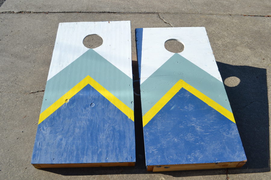 Two cornhole game boards painted in a chevron pattern in blue, yellow, sage green and white
