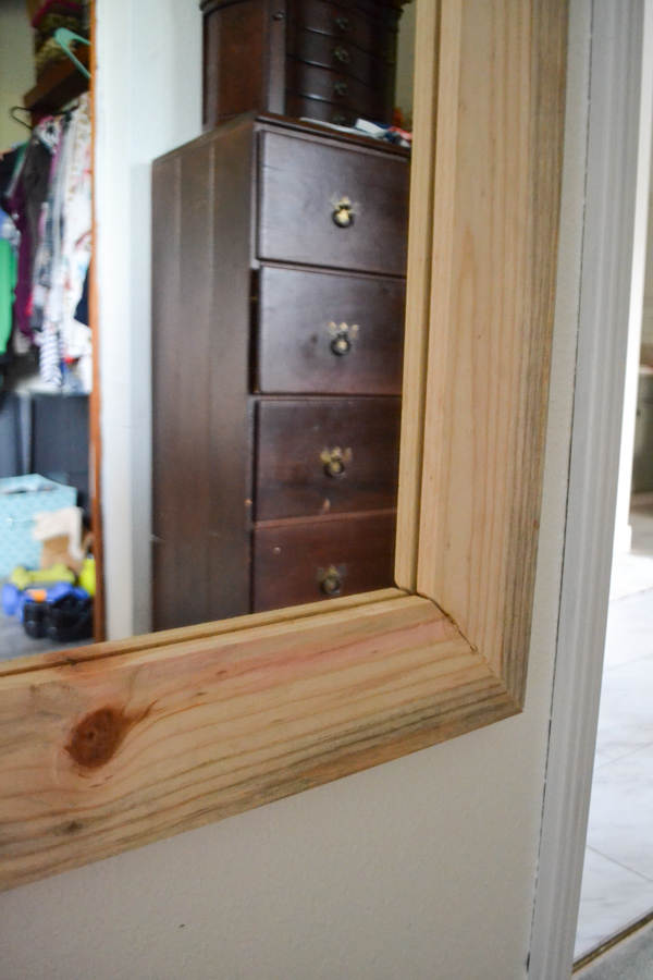 A close up of a corner of a full length mirror with a wood frame