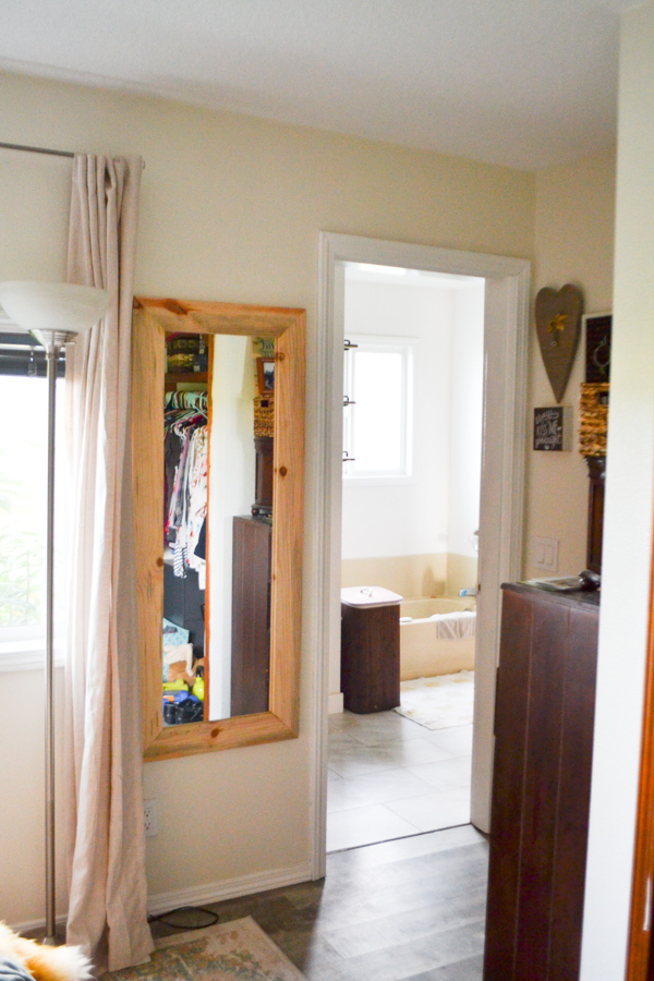 A full length mirror framed in wood hanging on a wall in a bedroom next to a door leading to a bathroom