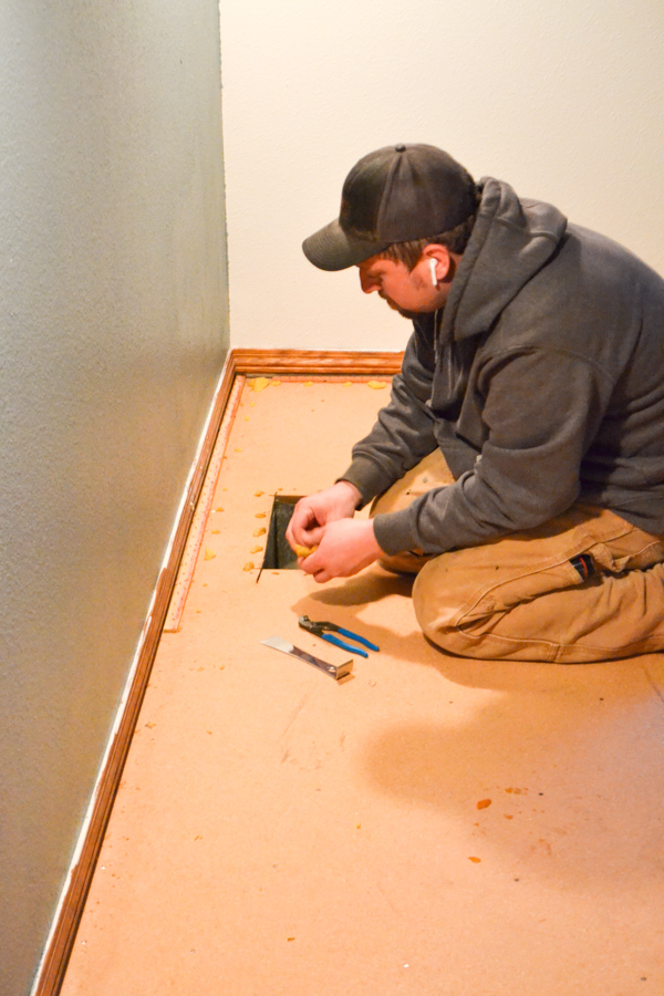 A man kneeling on the floor removing staples from a subfloor