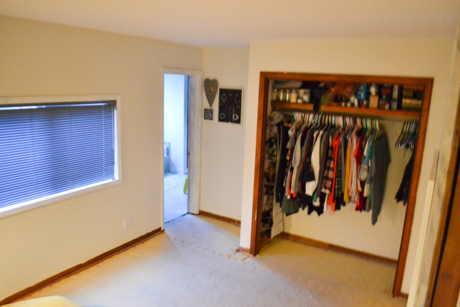 A wide shot of a bedroom, with a closet with no doors and a subfloor with trim still attached