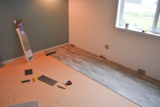A wide shot of a bedroom with a window on the upper right and partially installed vinyl flooring