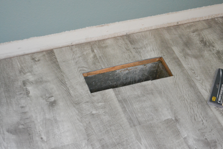 A close up of a heat vent opening with vinyl plank flooring installed surrounding it
