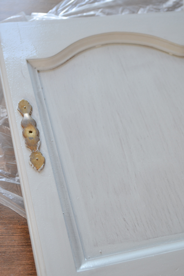 A close up of a hutch door with one coat of blue gray milk paint