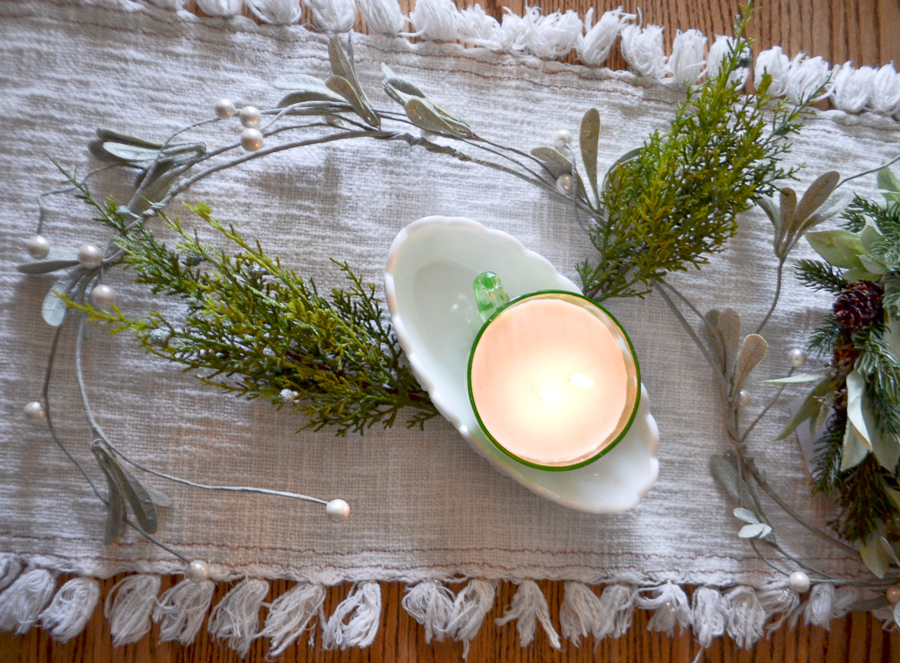 An above view of a soy teacup candle in a milk glass tray with faux greenery on a white table runner